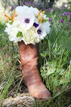 cowboy boots under the wedding dress photographed with bridal bouquet. Precious!