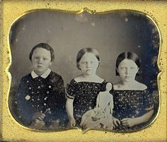 Three kids posed with their toys. 1800's