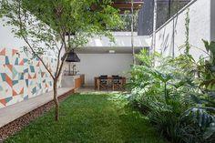 Decoração de casa geminada com luz natural. No jardim plantas, grama e mesa de jantar de madeira.