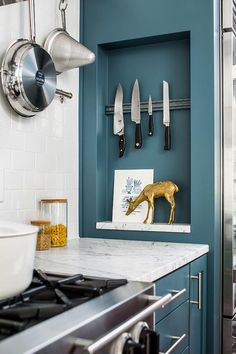 A magnetic knife rack and marble shelf are fixed in a rectangular niche positioned near a stainless steel oven range located against white subway backsplash tiles, beneath a wall mount pot rack, and beside blue cabinets adorned with long satin nickel pulls and a carrera marble countertop.