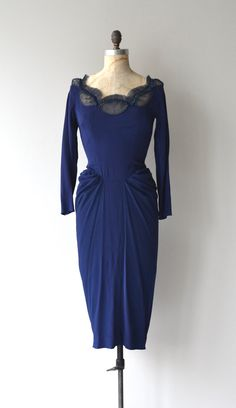 Fetching late 1940s, early 1950s navy blue rayon cocktail dress with tulle and beaded open neckline, slender sleeves, body-hugging contours, draped