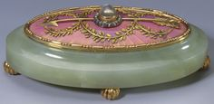 Oval bowenite two-coloured gold bell-push with convex oval top enamelled with guilloché salmon pink sunburst design and mounted with gold bead and reed borders and entwined green gold laurel garland. Mecca stone push surrounded by diamonds and sitting atop gold arrow.