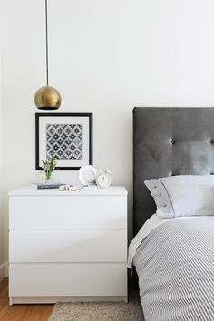 White and gray bedro White and gray bedroom features a dark gray tufted headboard on queen bed dressed in white and gray pinstripe bedding beside a brass dome pendant suspended from the ceiling and hanging over an Ikea Malm 3 Drawer Chest.