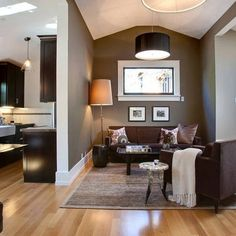 These light hardwood floors contrast dark brown furniture. The light lampshade and cream throw are nice accessories.