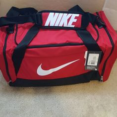 """Nike Duffel Bag NWT Red Bag is considered """"medium"""" duffle. Dimensions are 24.5"""" x 13"""" x 12"""".  Had adjustable strap and zippered pockets on sides. Also has wet/dry separation. Price is firm. Nike Bags Travel Bags"""