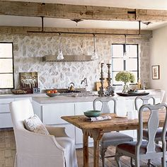 This kitchen capitalizes on the cottage exposed stonework to create a rustic and modern kitchen around the built-in backsplash.