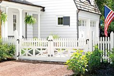 Charming Entry - Best Exterior Makeover - Southernliving. The expansive painted wood gate recalls the scale of those that lead to rural pastures. The X motif and rustic hardware offer more farmhouse authenticity.