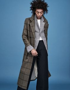 She wears a shirt and jacket by Hakuï, and a coat and trousers by Samuji.