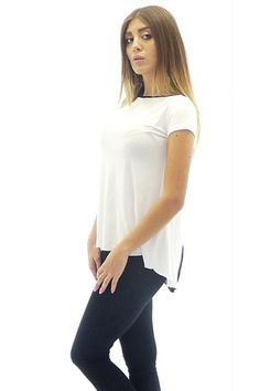 Asymmetrical women jersey tunic. The tunic is in white and has a flared cut. The model is with short French sleeves. The back of the tunic has a triangle piece of see-through black lace.