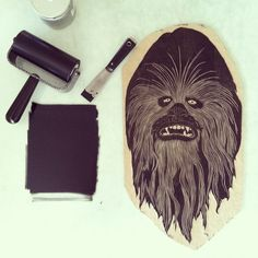 "Fun fact: Chewbacca, or Chewie as his friends liked to call him, died during the Yuuzhan Vong War. The mount of his head tributes his long life of loyalty, strength, and heroic actions. With a little bit of watercolor to bring out his blur eyes and dull teeth, this limited edition of 60 has been hand printed from an original woodcut onto rice paper, then pasted onto 3/4"" birch plywood and from there the exact image is sawed out, sanded, wired, and made ready for your wall. Bein..."
