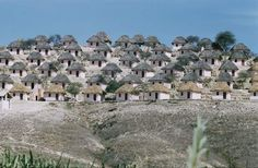 Houses with thatched roofs are clustered on a hillside in Angola.
