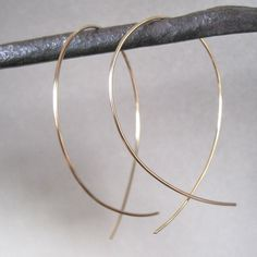 Here's a spin on traditional gold hoop earrings. These earrings are hand formed with an upside down loop. Available in gold, rose gold & silver. It's the perfect accessory to add a touch of simple ele