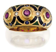 Ruby, sapphire, onyx, enamel and diamond ring, Cartier, circa 1994, of hoop design set to the centre with three circular-cut rubies within a buff onyx surround highlighted at intervals with similarly cut sapphires and diamonds, with enamel accents, mounted in 18ct gold, numbered C 94408, size 55/O, signed Cartier.