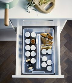 A shot from above of an IKEA SAMLA box filled with jars of herbs and spices in an open drawer.