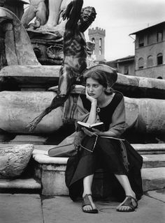 "A photograph from the famous ""American Girl"" series by Ruth Orkin. The photos, taken in Florence, depict a female tourist traveling through Italy in 1951. In this particular shot, she is sitting in front of the fountain of Neptune in Loggia of Piazza della Signoria."