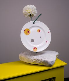 Rob Kessler / THE ODOUR OF CHRYSANTHEMUMS, 1998 A bone china plate with cut holes and printed daisy images, hung from a bronze cast of an ash branch with artificial chrysanthemum, supported on Carrara marble base.