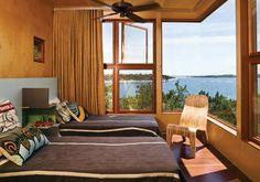 ETNICO AFRICANOSpessa, ruvida, dello stesso colore del legno delle pareti. La tenda scelta per oscurare la grande finestra angolare di questa casa di vacanza in Texas, è in grado di schermare la luce