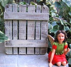 A little garden fairy poses in front of a miniature gate in her miniature fairy garden.