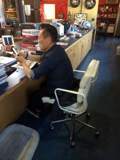 Internationally famous antique dealer, Joel Chen, hard at work buying and selling while sitting in his favorite chair, a new Herman Miller Eames Soft Pad in premium white leather.