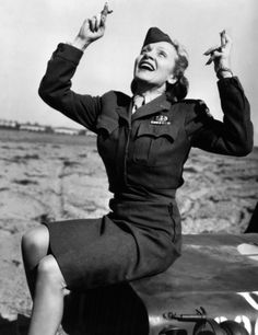 With victory near, Marlene Dietrich crosses her fingers while visiting American soldiers on the front lines in Europe, 1945