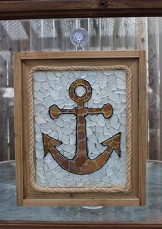 Handcrafted anchor mosaic sun catcher made from genuine sea glass. Since the mosaic is made from genuine sea glass, each individual piece is one a kind. This wooden framed sun catcher accented with nautical rope measures 12 3/4 by 10 3/4 and has a silver hook.