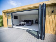 Inspiration 7x4m garden room, used as a cosy lounge and chill out room, with 4m Aluminium Folding Door Set.