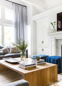 High ceilings, white walls, wooden waterfall coffee table, blue poufs, striped rug // Amber Interiors