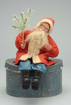 German Santa Claus with red robe, blue pants. He holds a small feather  tree .