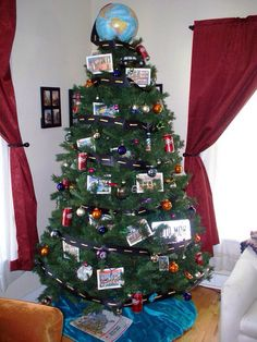 """The Road Trip Tree. A globe for a topper, with handmade road-ribbon for garland. Empty Dr Pepper cans, Matchbox cars, old license plates, and collected ornaments from various sites visited. Vintage """"Greetings From"""" postcard prints offer unique """"seasons greetings."""" Multicolored twinkle lights, jewel-toned filler ornaments, and a turquoise tree skirt. (7.5-ft. artificial tree)"""