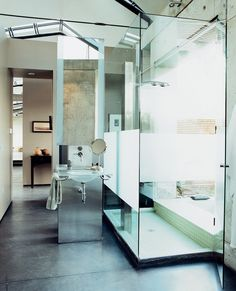Partially frosted glass shower enclosure + concrete floors.