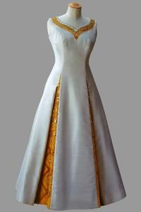 White crêpe shift with yellow beaded embroidery around sweetheart neckline    Norman Hartnell    First worn by Queen Elizabeth II for the State Visit to Thailand, February 1972. The yellow fabric and embroidery was designed to match the yellow sash of the Thai Order of Chakri.