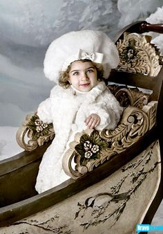 Victorian Christmas child in her white fur coat and hat, in a carved horse sleigh. Portrait is a Gia Giudice baby Christmas card #girl #snow #sleigh