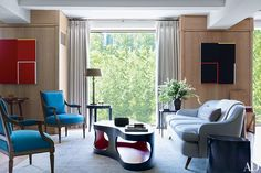 Fashion Designer Derek Lam's living room // In the living area, which overlooks Gramercy Park, vintage French armchairs and a sofa designed by Neal Beckstedt are grouped around a custom-made Jacques Jarrige lacquer cocktail table from Valerie Goodman Gallery. The vintage André Arbus table lamp is from Alan Moss, and the paintings are by Sylvan Lionni.
