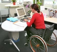 Disability refers to a person who has a disability if s/he has a physical or mental impairment which has a substantial and long-term adverse effect on that person's ability to carry out normal day-to-day activities.  In this picture we see a women taking care of daily work tasks with the help of a modified desk and a wheel chair.