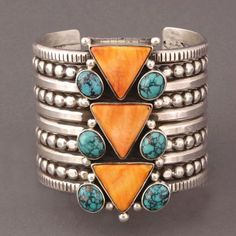 "Mike Bird Romero Bracelet of Turquoise and Spondylus - This is one of Marti Struever's personal favorites! A large silver bracelet by Mike Bird Romero is set with 3 spiny oyster triangles, each triangle is decorated by 2 natural turquoise circles and two silver beads for quite the fun geometric effect. , Mike Bird Romero has accented the silver cuff with four rows of silver beads. The large bracelet measures 2 5/8"" wide. The terminals open 1 1/4"" and the inside circumference is 5 1/4""."