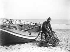A fisherman in sou'wester mending lobster/crab creels on the beach alongside a beached Sheringham crab boat. Maker: Smiths Suitall Ltd Date: circa 1910-11
