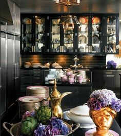 Entirely, utterly in love with this kitchen!  Luxe and dark- and the lilac porcelain, flowers, and gold accents are all the perfect counterpoints.