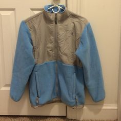 North Face Denali Girls XL Gently used North Face Denali fleece jacket in light blue and gray. Girls size XL which fits like a woman's small. I am a medium and I was able to wear it just the sleeves were a little short. One minor imperfection on the back (shown in the last picture along with my pinky finger for size comparison). No holes or fraying or pulling. Great jacket I'd still be wearing if I didn't just get a new one in a different color. Smoke free and pet free home. Questions?…