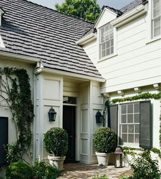Better Homes & Gardens.  our house. :).  from bhg:  Colonial details, such as wood shingles, pedimented upper windows, and lantern sconces flanking the front door, give this home character. A brick path and growing ivy add charm.