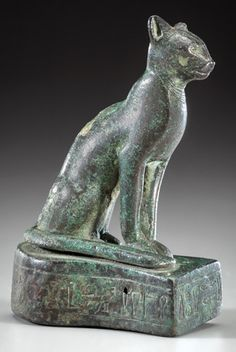 """Egyptian Bronze Seated Cat Goddess Bastet. Third Intermediate Period, Dynasty XXII, circa 900-800 BC.  Hieroglyphic inscription around integral base: """"May Bastet the great, Lady of Bubastis, give life to the god's father, priest of Bastet Hor-Khebit, son of Pen wa-wer.."""" This and other important ancient art on CuratorsEye.com"""