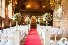 Aisle plinths with tall vase arrangements at Peckforton Castle
