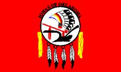 """The flag of the Iowas that reside in Oklahoma is red and bears the tribal seal in the center (Annin & Co.). On top of the seal in black is """"IOWAS OF OKLAHOMA"""". Within the white seal are two symbols common to many Native American peoples: the headdress, which appears in light blue, red, white, and black, and the peace pipe, in black with a yellow streamer"""