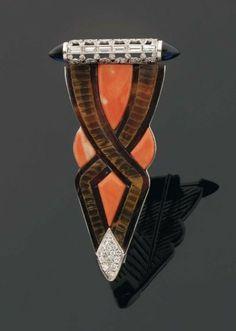 RARE CLIP en forme de flèche stylisée en écaille soulignée de motifs de corail. La barrette supérieure est composé d'un treillage de diamants brillantés et baguette souligné de pierres bleues. Monture en or gris et platine. Années 1930.