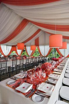 Coral and orange table runners and centerpieces add a splash of color to crisp white linens.