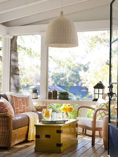 This sunny screened porch welcomes visitors with an eclectic collection of furniture and accessories. The cozy seat cushion atop the wicker sofa provides the perfect spot for relaxing. A trunk-turned-coffee table offers a surface to place a tray of drinks as well as a hidden storage area for blankets and spare pillows./