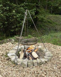 Eine sehr einfache Runde Feuerstelle mit Steinen erstellt enthält eine hängende Kochen Rost ausgesetzt von Tipi-Struktur.