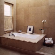 an undermount tub covered by a beautiful slab of marble. It is such a gorgeous, timeless design