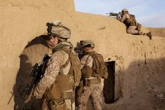 Photo by USMC Sgt Bobby J. Yarbrough: U.S. Marine Lance Cpl. Emilio Therien Gonzales, right, climbs on top of a compound to try and locate a shooter who fired on U.S. Marines with the 2nd Battalion, 7th Marine Regiment while they were conducting a sweep of a compound near Patrol Base Boldak, Helmand province, March 3.