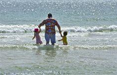 Hands full; at the beach; Glenelg, South Australia, Australia.  January 2014.