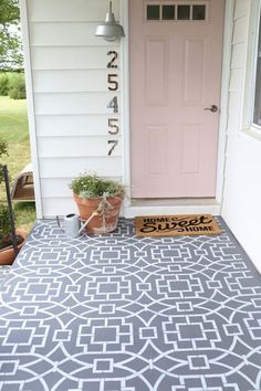 I love this front porch! Stenciled floor, pale pink door, fun house numbers